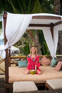 Portrait of happy woman with coconut kneeling on four-poster bed at beachの写真素材 [FYI03737198]