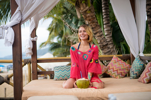Happy woman with coconut kneeling on four-poster bed at beachの写真素材 [FYI03737202]