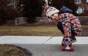 Portrait of boy skateboarding on footpath at parkの写真素材 [FYI03737250]