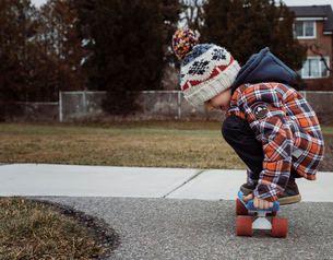 Side view of boy skateboarding on footpath at parkの写真素材 [FYI03737251]