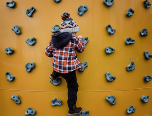 Rear view of boy climbing wall at health clubの写真素材 [FYI03737253]