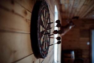 Dartboard hanging on wooden wallの写真素材 [FYI03737277]
