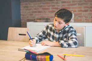 Boy coloring on spiral notebook with colored pencil at table in homeの写真素材 [FYI03737289]
