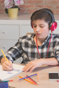 Boy listening music while coloring on book with colored pencil at table in homeの写真素材 [FYI03737292]