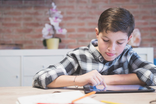 Boy sticking out tongue while drawing on tablet computer at tableの写真素材 [FYI03737293]