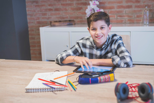 Portrait of smiling boy with tablet computer on table at homeの写真素材 [FYI03737294]