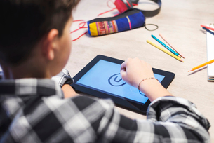 Close-up of boy drawing on tablet computer at tableの写真素材 [FYI03737295]