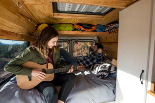 Woman playing guitar while sitting with friend in motor homeの写真素材 [FYI03737358]