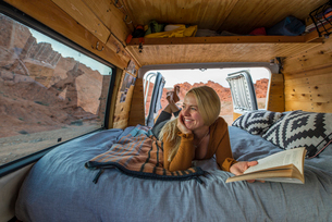 Happy woman holding book while looking through window in motor homeの写真素材 [FYI03737363]