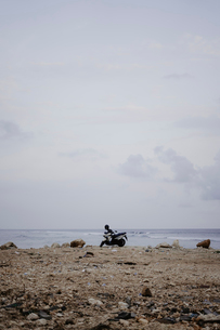 Mid distance view of motor scooter parked at beach against skyの写真素材 [FYI03737365]