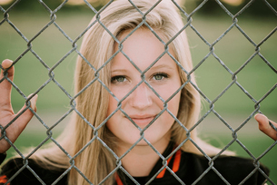 Portrait of softball player standing by fence at playing fieldの写真素材 [FYI03737391]