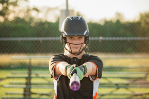 Portrait of softball player holding baseball bat while standing at playing fieldの写真素材 [FYI03737392]