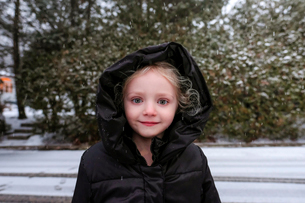 Portrait of cute girl wearing hooded jacket during winterの写真素材 [FYI03737397]