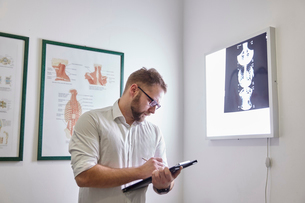 Male doctor writing while standing in medical clinicの写真素材 [FYI03737505]