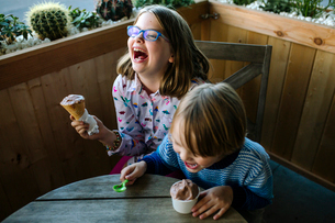 High angle view of happy siblings eating ice cream while sitting in cafeの写真素材 [FYI03737622]