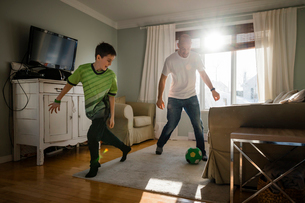 Father with son playing soccer at homeの写真素材 [FYI03737736]