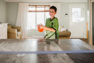 Happy boy playing table tennis at homeの写真素材 [FYI03737738]
