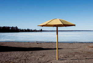 Parasol by frozen lake against clear sky during winterの写真素材 [FYI03737946]