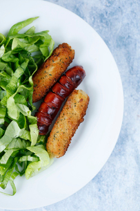 Overhead view of chopped lettuce with mozzarella sticks and sausage served in plate on tableの写真素材 [FYI03738220]