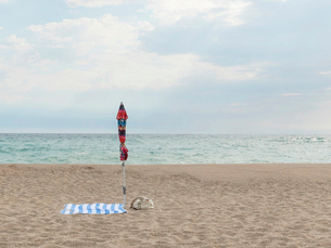 Parasol and towel at beach against skyの写真素材 [FYI03738447]
