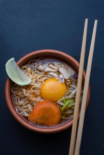 Overhead view of instant noodles soup served in bowl with chopsticks on tableの写真素材 [FYI03738503]