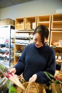 八百屋で有機野菜を選ぶ女性の写真素材 [FYI03738846]