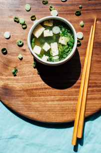 High angle view of soup bowl with chopsticks on serving board in commercial kitchenの写真素材 [FYI03738873]