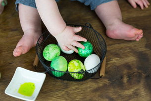 Midsection of baby boy playing with colored Easter Eggs in metallic basket on hardwood floor at homeの写真素材 [FYI03739124]