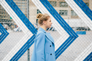 Side view of young woman wearing trench coat while walking against metallic fence in cityの写真素材 [FYI03739154]