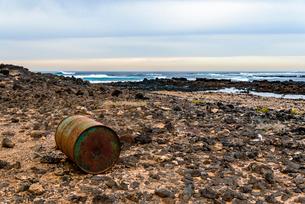 Rustic metallic barrel at rocky beach against cloudy skyの写真素材 [FYI03739203]