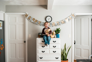 Full length of playful birthday boy with number helium balloon sitting on cabinet at homeの写真素材 [FYI03739242]