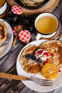 Close-up of pancakes with preserves and fruits on wooden tableの写真素材 [FYI03739258]