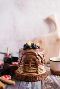 Stack of pancakes with chocolate and fruits on woodの写真素材 [FYI03739260]
