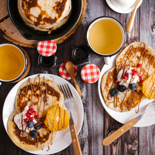 Overhead view of pancakes with preserves and fruits on wooden tableの写真素材 [FYI03739262]