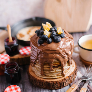 Stack of pancakes with chocolate and fruits on wood at tableの写真素材 [FYI03739271]