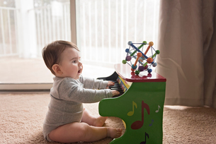 Side view of curious baby boy playing toy piano at homeの写真素材 [FYI03739394]
