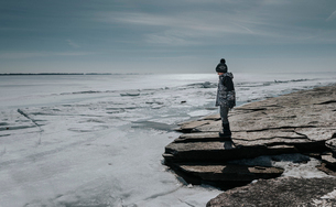 Side view of boy standing by frozen sea against skyの写真素材 [FYI03739468]