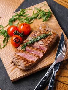 High angle view of cooked meat with ingredients on cutting boardの写真素材 [FYI03739479]