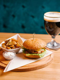 Close-up of burger served with drink on wooden tableの写真素材 [FYI03739490]