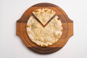 Overhead view of pizza on wooden serving board over white backgroundの写真素材 [FYI03739517]