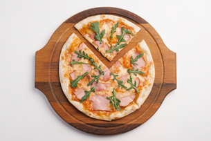 Overhead view of pizza on serving board over white backgroundの写真素材 [FYI03739520]