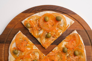 Close-up of pizza on wooden serving board over white backgroundの写真素材 [FYI03739521]