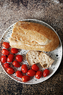 Overhead view of bread with cherry tomatoes in plate on tableの写真素材 [FYI03739862]