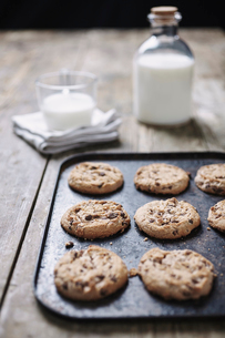 Close-up of chocolate chip cookies on baking sheet with milk over wooden tableの写真素材 [FYI03739880]