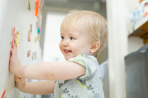Smiling baby boy playing with colorful magnetic letters on metallic cabinet at homeの写真素材 [FYI03739890]