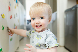 Portrait of cute smiling baby boy playing with colorful magnetic letters on metallic cabinet at homeの写真素材 [FYI03739891]