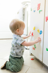 Side view of baby boy playing with colorful magnetic letters and numbers on metallic cabinet at homeの写真素材 [FYI03739892]