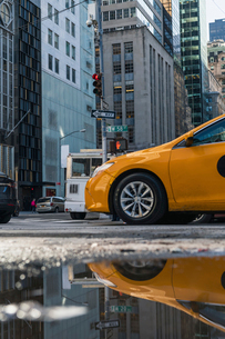 Taxi reflecting on puddle in city during rainy seasonの写真素材 [FYI03739905]