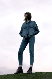 Full length of confident young woman with hands in pockets standing on field against skyの写真素材 [FYI03739943]