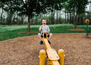 Portrait of happy boy playing on seesaw at parkの写真素材 [FYI03740066]
